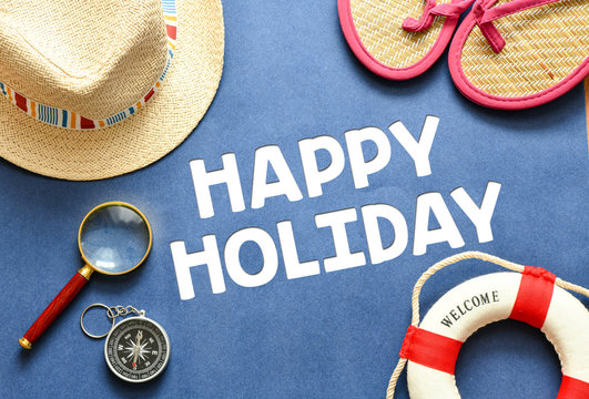 Happy Holiday text. Travel and summer concept with life saver, magnifying glass, flip flops, compass and hat.