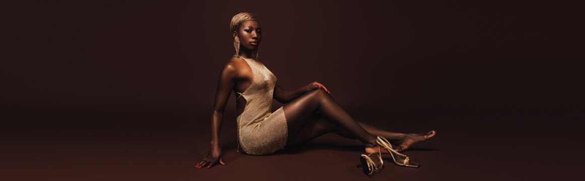 seductive african american woman with short hair posing in glamorous dress on brown