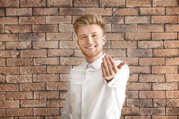 Handsome young man inviting viewer against brick background