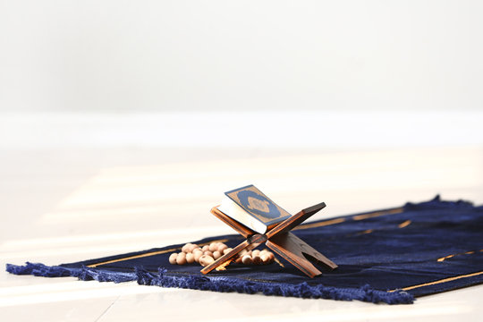 Koran and tasbih on Muslim prayer mat