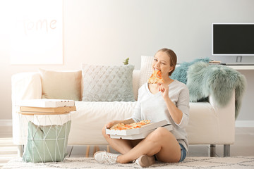 Beautiful woman eating tasty pizza at home Wall mural