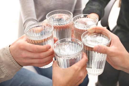 Group of people drinking water indoors, closeup