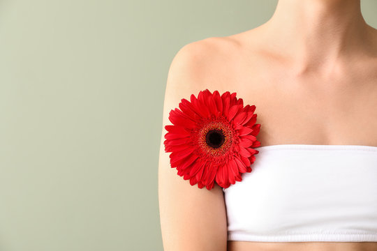 Beautiful young woman with flower on color background. Depilation concept