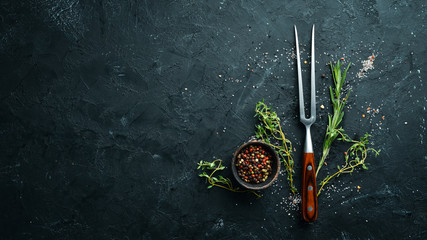 Fork for meat, spices and herbs on a black stone table. Top view. Free space for your text.