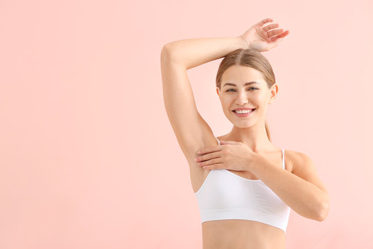 Beautiful young woman with smooth skin after depilation on color background