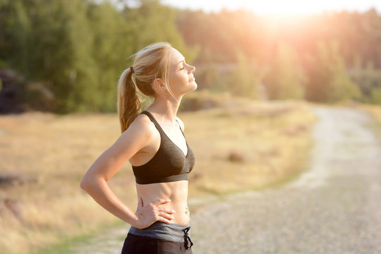 Sporty woman enjoys the sun after running and workout on a sunny summer day