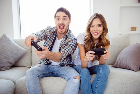 Portrait of his he her she two person nice-looking attractive lovely cheerful cheery positive guy lady playing online station having fun in light white style interior hotel house indoors