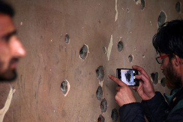 A man uses his mobile phone to take pictures of a bullet-riddled wall of a residential house that was damaged during a gun battle between Zakir Rashid Bhat and Indian security forces on Thursday, in Dadasara