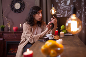 Portrait of shocked young woman sitting at a bar counter in a coffee shop looking at her phone
