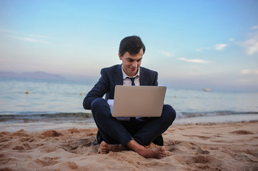 close up photo of a young man in suit with laptop working on the beach and talking to someone Wall mural