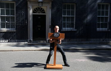 A staff member arranges a podium outside 10 Downing Street, as Theresa May is expected to make a statement, in London
