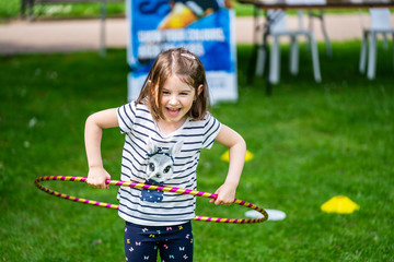 Happy little girl playing with hula hoops on a sunny day in park