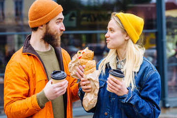 Funny surprised beard hipster man feeding blond hungry caucasian woman with sandwich outdoors in cold spring weather at city street outdoor. Couple wearing orange, blue jeans jackets and yellow hat. Wall mural