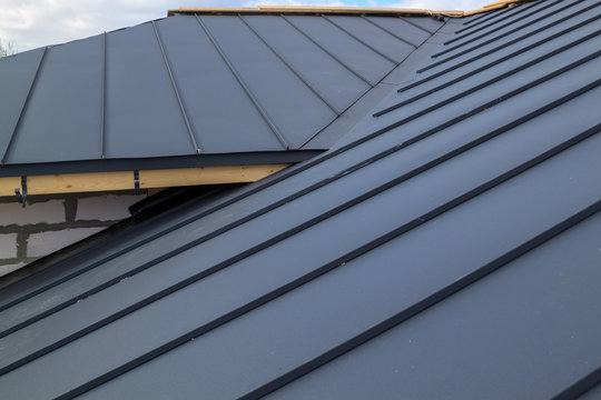 close up view of  house under construction with grey folding roof on waterproofing layer