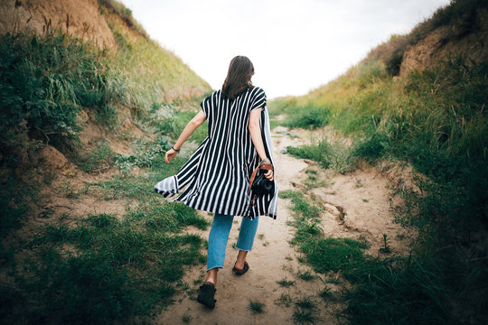 Stylish hipster girl running on sandy cliff  to sea and holding photo camera.  Happy young boho woman exploring tropical island at sandy cliff beach. Summer vacation. Space for text.