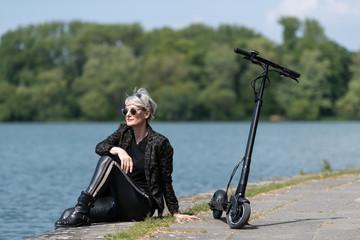 Frau mit e-Scooter sitzt am Seeufer in der Stadt
