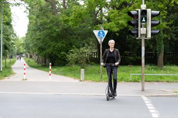 Frau fährt mit Elektroroller über Fußgängerüberweg mit Ampel