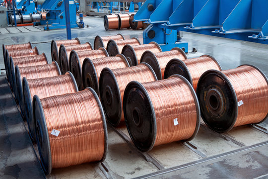 Several rows of new finished coils with copper wire in the production shop. Copper wire is wound on metal coils or drums. Modern line of automatic production of electric cable and wire.