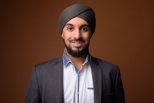 Young bearded Indian Sikh businessman wearing turban against bro