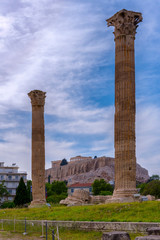 Athens, Attica / Greece. The Temple of Olympian Zeus also known as the Olympieion or Columns of the Olympian Zeus. Between the ancient columns the Acropolis of Athens with the Parthenon. Cloudy sky