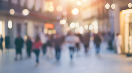 Group of unrecognizable anonymous people in bokeh walking on a street in the evening. Defocused image