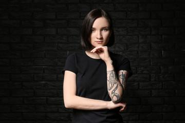 Beautiful tattooed woman on dark background