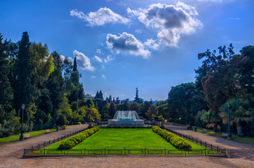 Athens, Attica / Greece. The garden with the marble fountain in front of the Zappeion Hall neo-classical building in the National Garden near Syntagma Square. Sunny day, cloudy sky, nobody