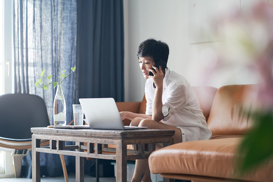 Asian self employed woman sitting on couch  & working on laptop at home