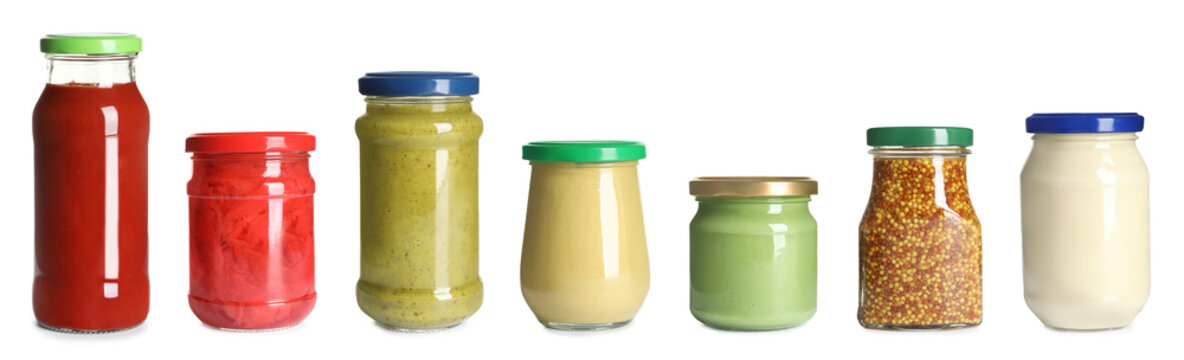 Set of glass jars with different delicious sauces on white background