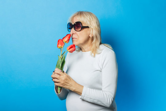 Old woman in sunglasses is holding a bouquet of tulips on a blue background. Concept of the onset of spring, summer time, vacation, camping