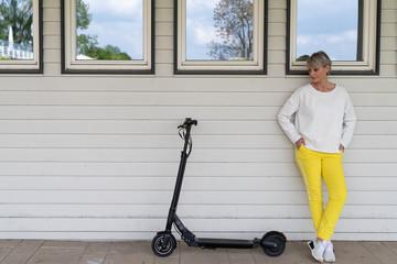 Sportliche Frau mit Elektroroller vor Hauswand