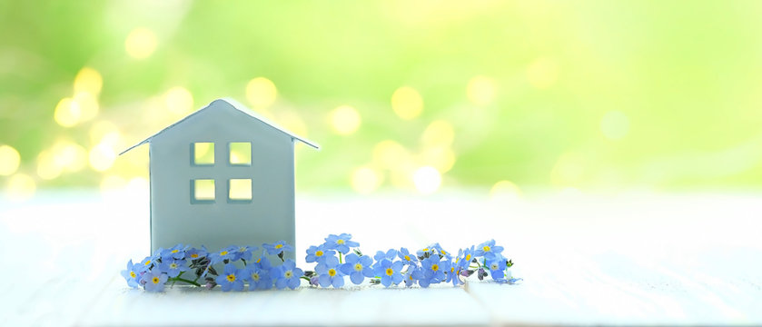 mini toy house and blue flowers. house on spring nature background. concept of mortgage, construction, rental, using as family and property concept. banner, copy space