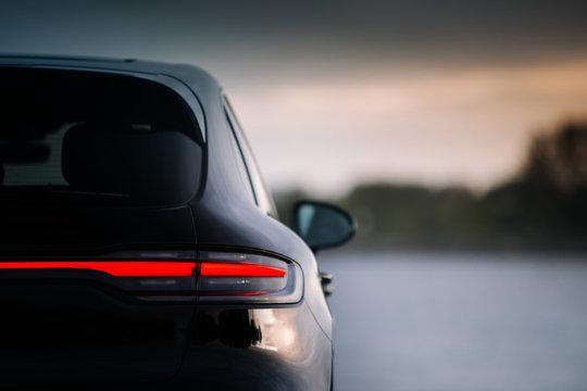 Modern suv car rear taillamp at evening near lake
