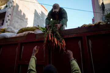 Men unload carrots on a street market in downtown Havana
