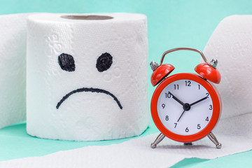 Constipation, indigestion, digestion problem. Alarm clock and toilet paper with sad face. Сreative concept