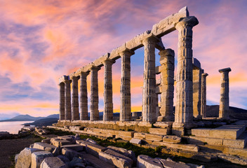 Sounion, Attica / Greece. The Temple of Poseidon at cape Sounion. Colorful sunset with beautiful cloudy sky. Golden hour