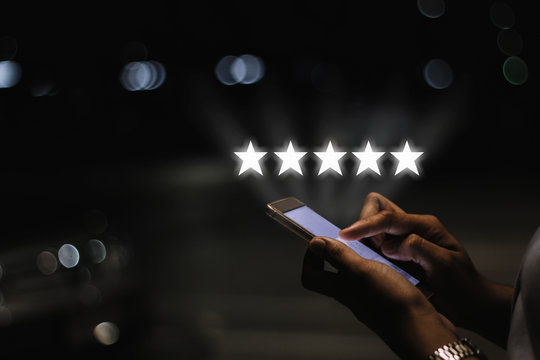 Businesswoman pressing five stars (5) rating on virtual touch screen at smartphone .Customer service evaluation concept.