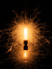 Light bulb with sparklers from behind on black background