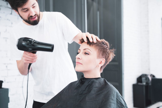 Hairdresser drying hair to woman