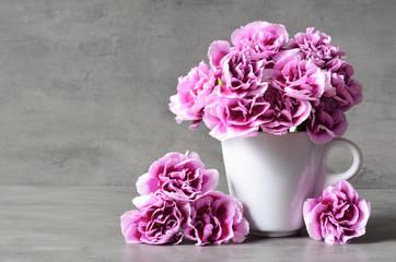 Obraz Pink carnation flowers in cup on grey background. - fototapety do salonu