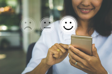 Wall Mural - Businesswoman pressing face emoticon on virtual touch screen at smartphone .Customer service evaluation concept.