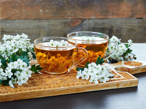 Pair of herbal healing flower tea from hawthorn bloom with blossom of  a tree nearby on wooden board on rustic background, closeup, copy space, alternative medicine concept