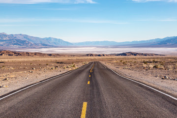 Looking down a road leading into Death Valley in California, with salt flats and a vast landscape ahead