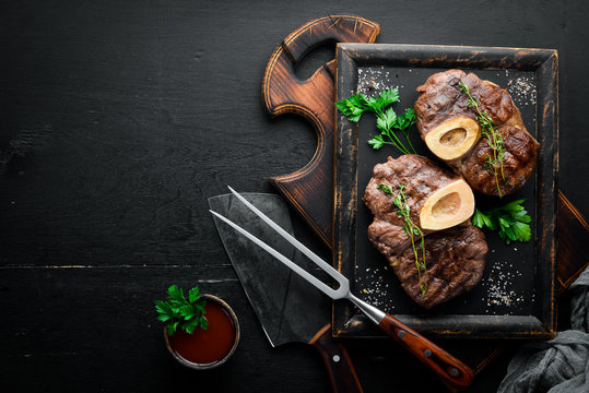 Beef shank roasted on a grill on a wooden background. Top view. Free space for your text.
