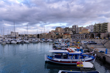 Heraklion, Crete Island - Greece. View to the old Venetian port with the traditional fishing boats and the Heraklion city with the old Venetian shipyards. Sunset, cloudy sky