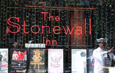 A U.S. Navy sailor takes a photo of the historic gay bar the Stonewall Inn during Fleet Week in New York City