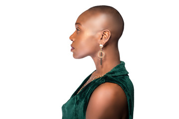 Beautiful black African American female model posing confidently with bald hairstyle on a white background.  The woman is portraying uniqueness and individuality.