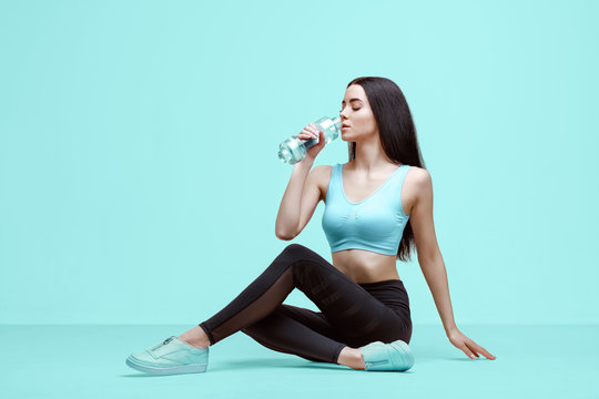 Amazing woman in trendy sportswear drinking water from bottle to stay hydrated after workout. Beautiful slim brunette young girl in fashion leggings and top on blue background.
