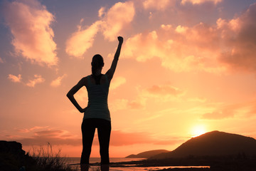 silhouette of young strong victorious woman with fist in the air at sunset