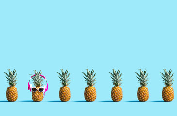 Wall Mural - One out unique pineapple wearing headphones on a solid color background